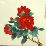 Red Camellia blossoms on a branch.